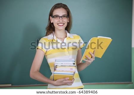 Teacher in front of blackboard holding books
