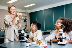 Teacher in protective eyeglasses showing reagents flasks for making experiments at school lab during chemistry science lesson class