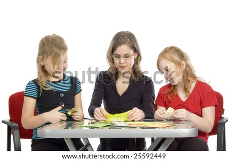teacher is showing two little girls how to diy on white