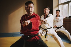 Teacher looking at camera with students during karate training. Pupils in a white kimono stand in a stance and train with the teacher.