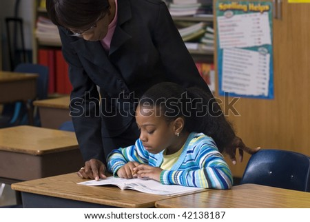Teacher looking over students shoulder, as she works on her workbook in the class room
