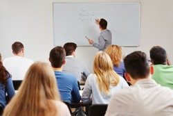 Teacher on whiteboard in class teaching business studies in university