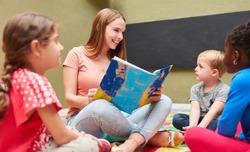 Teacher or childminder reading from a children's book in kindergarten