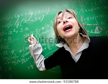 Teacher pointing at blackboard teaching mathematics