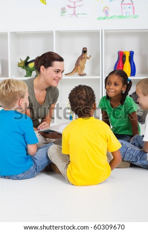 teacher reading book to preschool students - stock photo