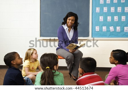 Teacher reading book to young students in classroom. Horizontally framed shot.