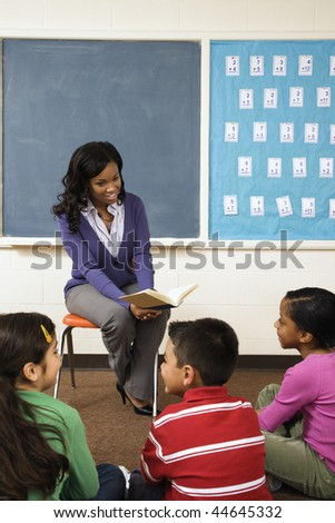 Teacher reading book to young students in classroom. Vertically framed shot.