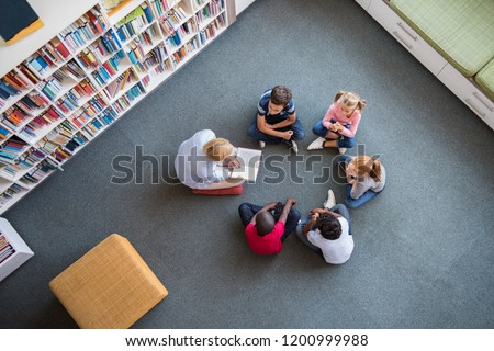 Teacher reading fairy tales to children sitting in a circle at library. Top view of librarian sitting with five multiethnic children on floor. Teacher reading book to girls and young boys at school.