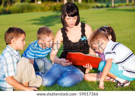 Teacher reading to her students - stock photo