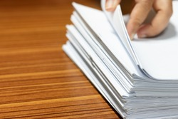 Teacher searching homework assignment on wood desk in school office for score, managed and inspected. Pile of unfinished paperwork. Report and notebook papers stacked. Business and education concept.