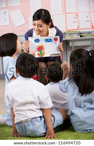 Teacher Showing Painting To Students In Chinese School Classroom - stock photo