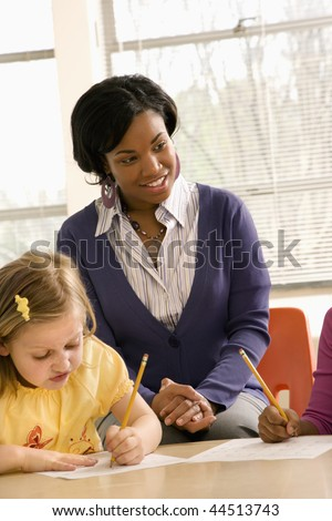Teacher smiling and helping students with schoolwork in school classroom. Vertically framed shot.