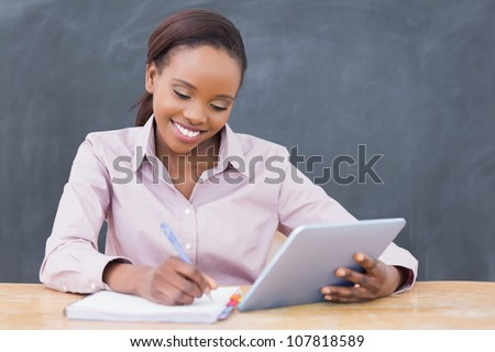 Teacher smiling while holding a tablet computer in a classroom
