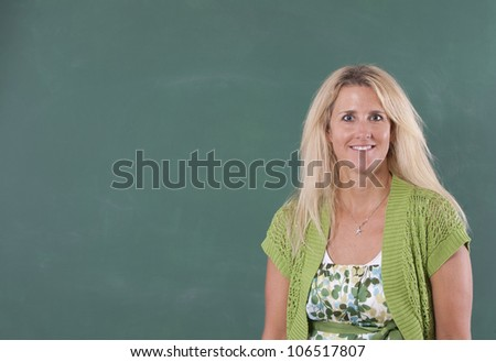 Teacher standing in front of chalkboard of classroom. Copy space can be used on chalkboard.