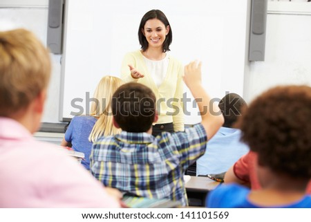 Teacher Standing In Front Of Class Asking Question