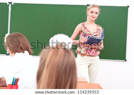 teacher stands in front of students in the class