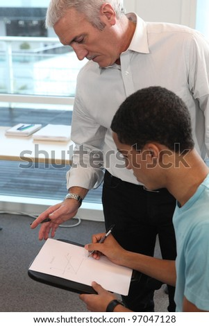 Teacher supervising his student's work