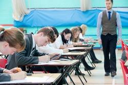 Teacher supervising middle school students taking examination at desks in school gymnastics hall