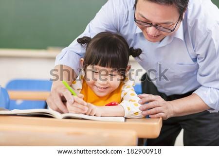 Teacher teaches a student to using a pencil