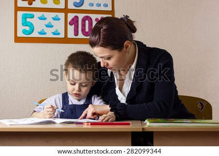 teacher teaches a young child at a school desk