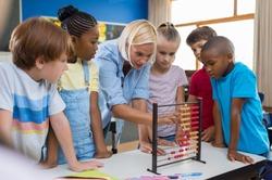Teacher teaching children math on abacus. Mature mathematics teacher helping schoolchildren use wooden abacus. Group of multiethnic kids understanding maths in classroom.