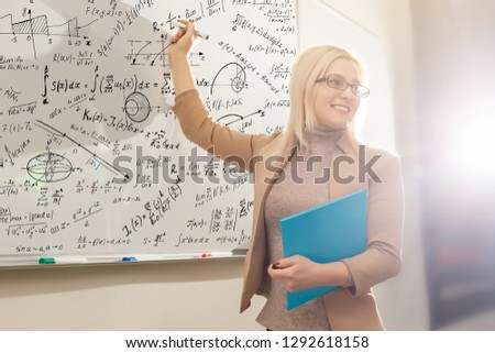 Teacher teaching how to count on whiteboard in classroom. Smiling blonde woman explaining additions in column in class. Math's teacher explaining arithmetic sums to elementary children.