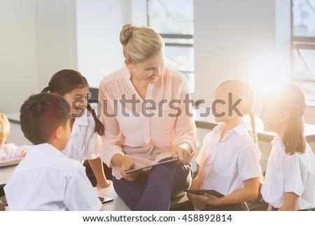Teacher teaching kids on digital tablet in classroom at school