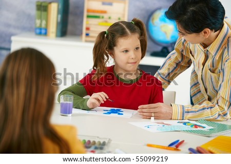 Teacher teaching painting to elementary age pupils in classroom at primary school.?