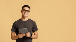 Teacher, tutor, blogger or student. Cheerful young attractive man in glasses looks at camera, holds digital tablet on online lesson, isolated on light background, panorama, empty space, studio shot
