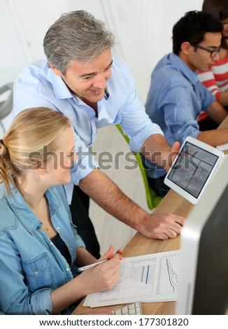 Teacher using digital tablet in school class