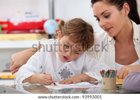 Teacher watching her pupil coloring a drawing