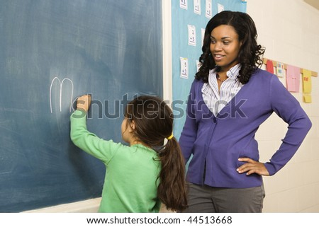 Teacher watching young female student write on blackboard. Horizontally framed shot.