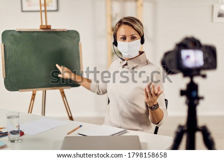 Teacher wearing face mask while giving online lecture and live streaming from home during COVID-19 epidemic.
