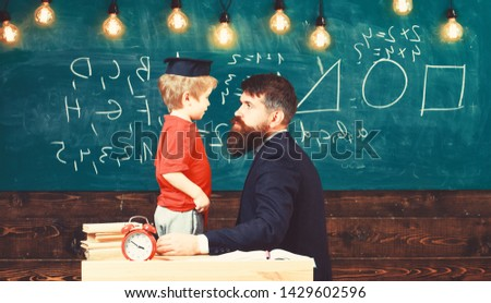 Teacher with beard, father teaches little son in classroom, chalkboard on background. Boy, child in graduate cap play with dad, having fun and relaxing during school break. School break concept.