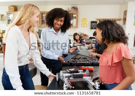 Teacher With Female Pupils Building Robotic Vehicle In Science Lesson #1131658781
