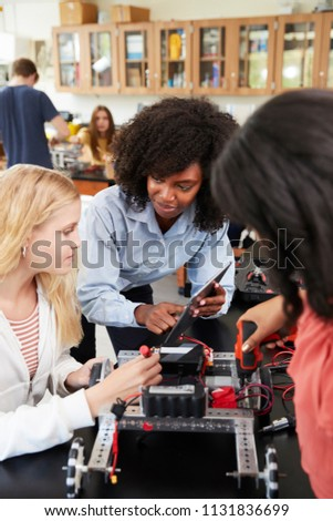 Teacher With Female Pupils Building Robotic Vehicle In Science Lesson #1131836699