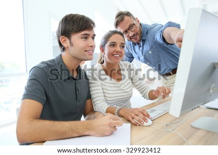 Teacher with group of students in class working on desktop stock photo