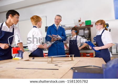 Teacher with high school students in design and technology class