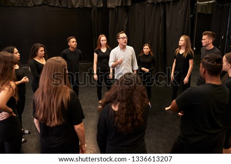 Photo of  Teacher With Male And Female Drama Students At Performing Arts School In Studio Improvisation Class