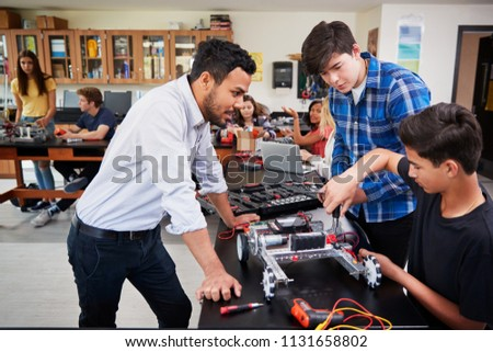 Teacher With Male Pupils Building Robotic Vehicle In Science Lesson #1131658802