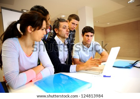 Teacher with students in class working on laptop - stock photo