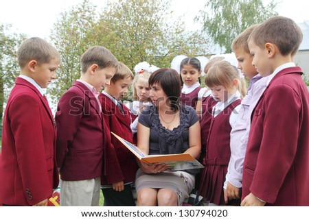 Teacher with students reading a book