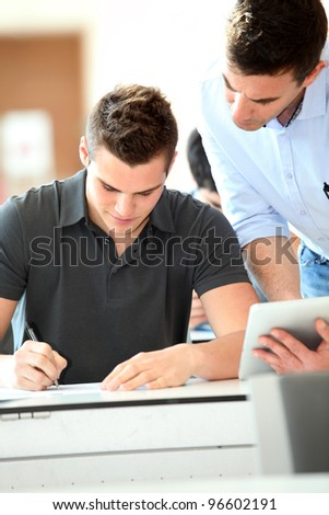 Teacher with tablet helping student with exam