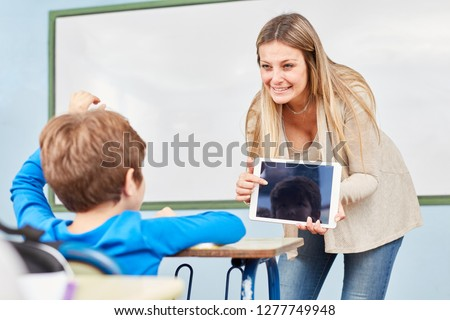 Teacher with tablet PC teaches a student in computer science class