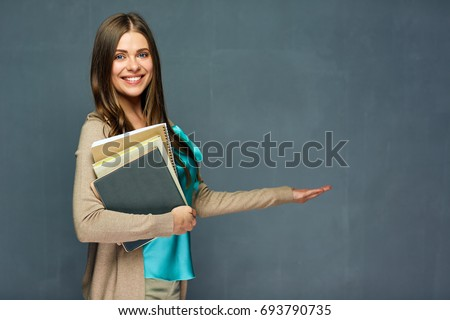 Teacher woman holding empty hand for product. Gray wall background.