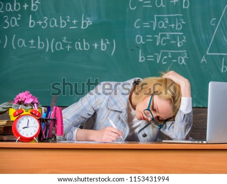 Teacher woman sit table classroom chalkboard background. Still working. Work far beyond actual school day. Teacher tired face keep working after classes. Teacher busy with paperwork and research.