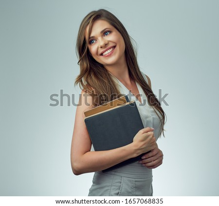 teacher woman with long hair holding books looking away. isolated female portrait.