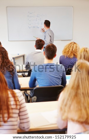Teacher writing financial mathematics formulas on whiteboard in university