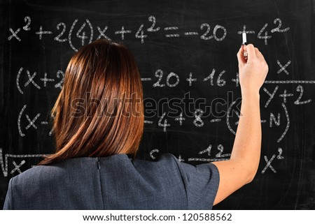 Teacher writing formulas on a blackboard