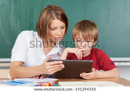 Teaching a boy with a tablet in classroom